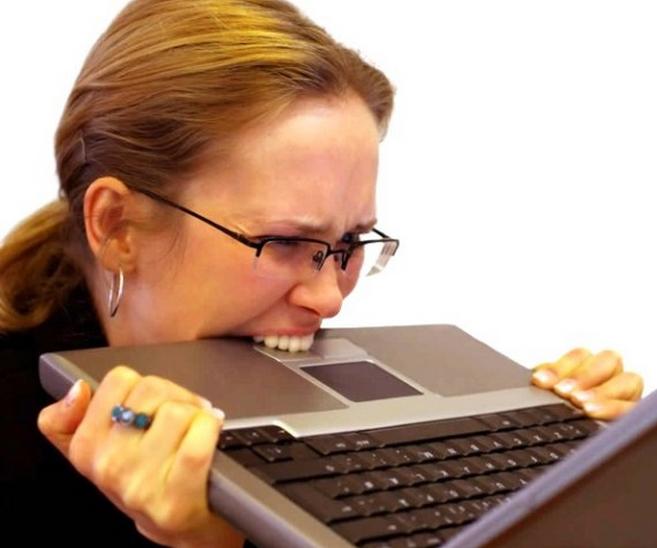 Mulher estressada mordendo notebook