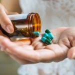 cápsulas de remédio na mão