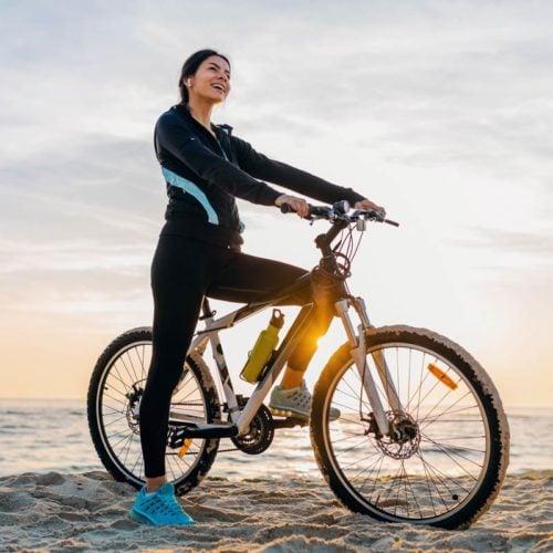 mulher na praia sentada em uma bicicleta