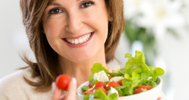 Mulher adulta comendo salada