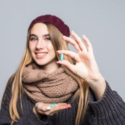 mulher segurando uma cápsula de pycnogenol