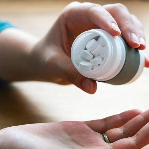 mulher colocando comprimidos na mao