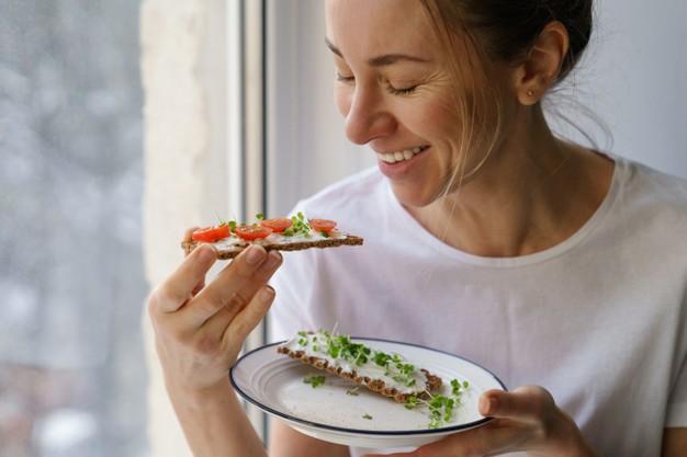 mulher comendo broto de alfafa