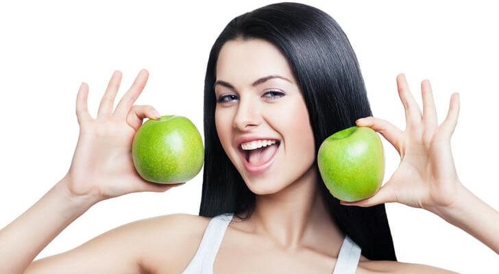 Mulher de cabelo liso segurando maçã