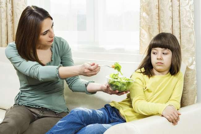 Mãe dando vegetais a filha