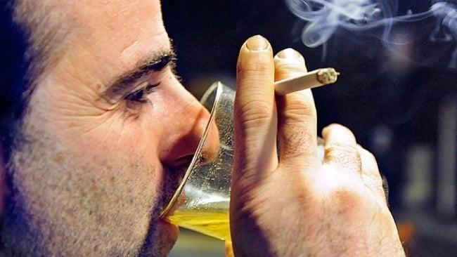 Homem bebendo e fumando