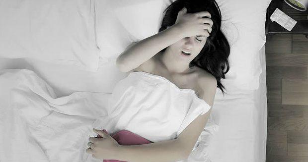 Mulher deitada com dores