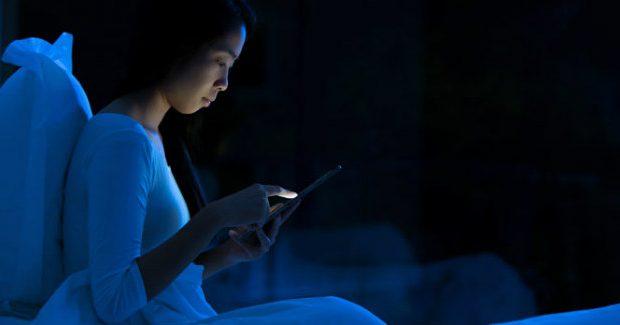 Mulher no celular à noite