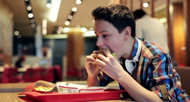 Adolescente comendo fast food
