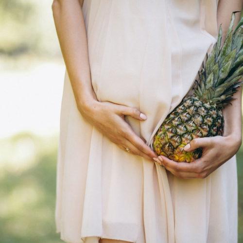 grávida segurando um abacaxi