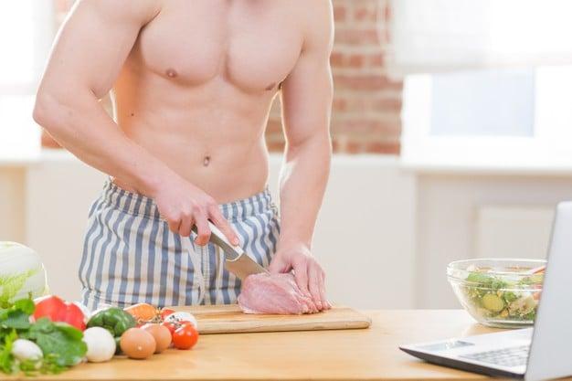 homem musculoso cortando o frango