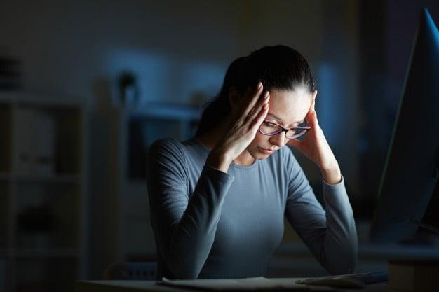 mulher cansada na frente da tela do computador