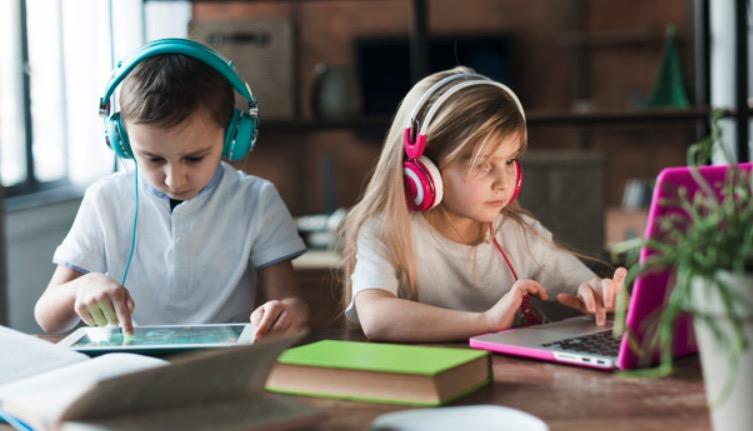 niños usando tableta y cuaderno