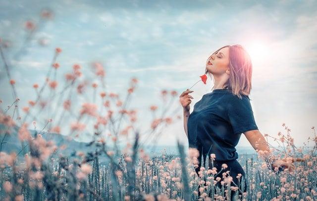 mulher andando relaxada em campo de flores