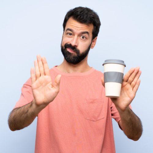 homem gesticulando para parar de tomar café