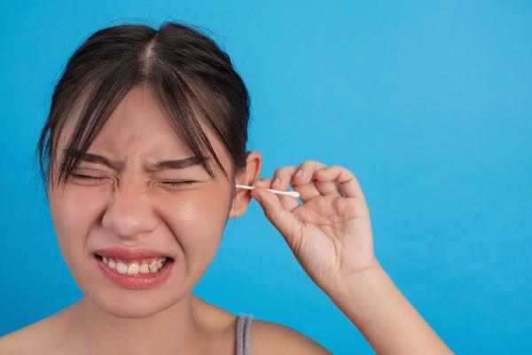menina cutucando o ouvido com cotonete