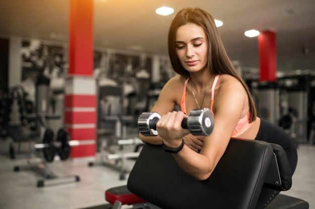 mulher fazendo rosca bíceps concentrada no banco
