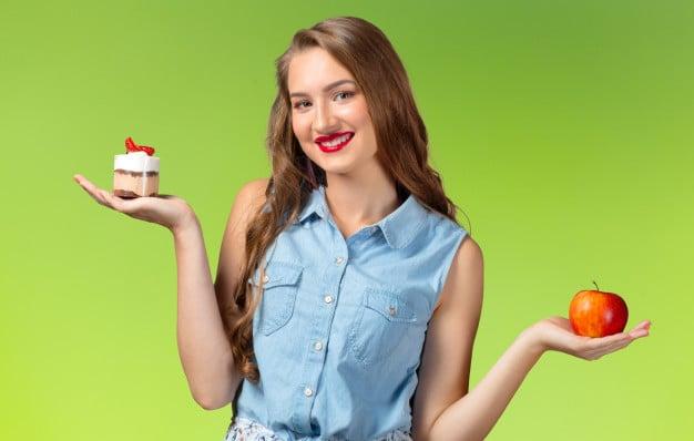 mulher na dúvida entre comer maçã ou bolo