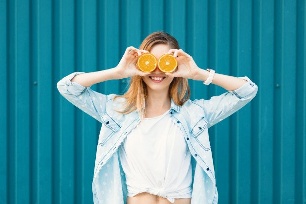 mulher segurando uma laranja que é fonte de vitamina C