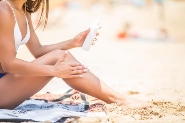 mulher passando protetor na praia
