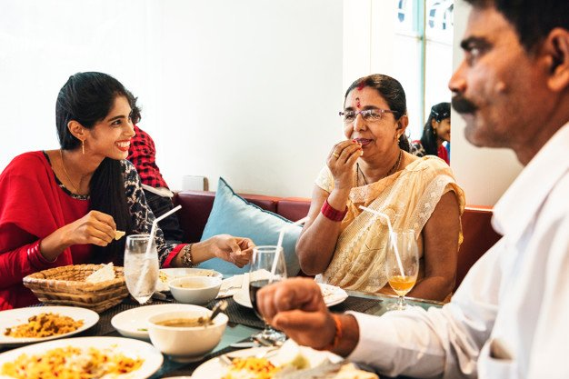 família indiana comendo na mesa