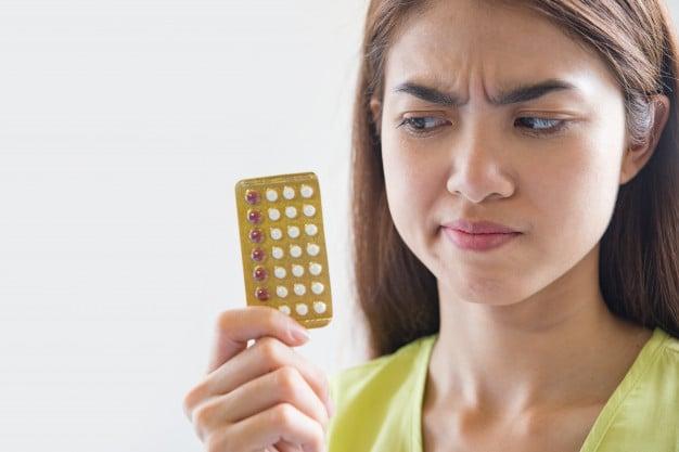 mulher segurando a cartela de pílula