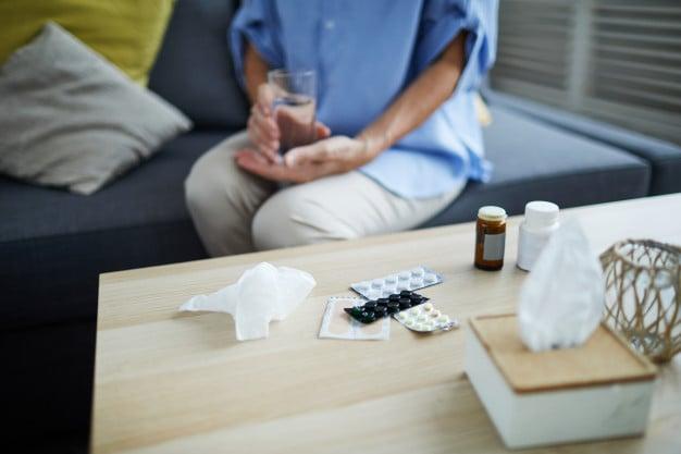 mulher sentada na cama toando remédios