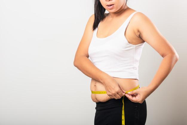 mulher medindo com fita métrica a barriga