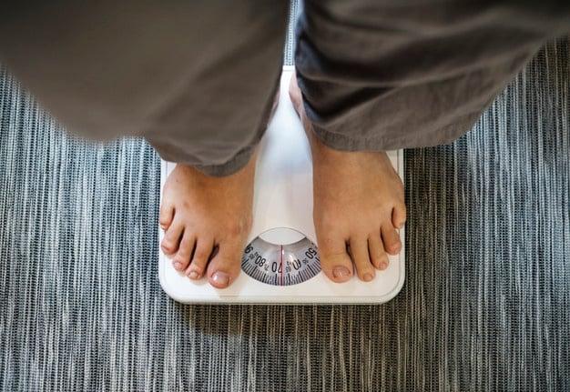 ganho de peso mulher em cima da balança