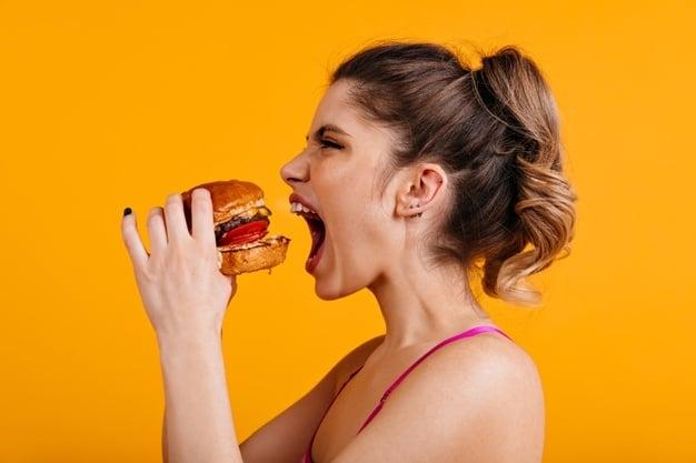mulher comendo hambúrguer