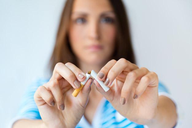 mulher cortando o cigarro ao meio