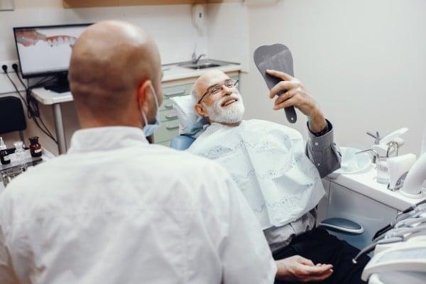 homem feliz no dentista