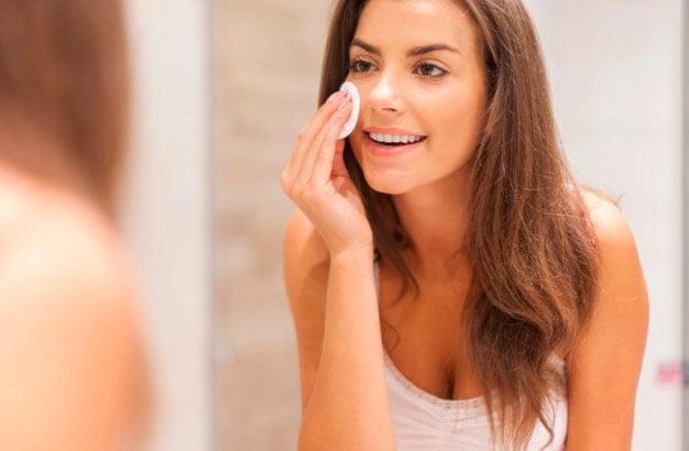 mulher cuidando da pele na frente do espelho